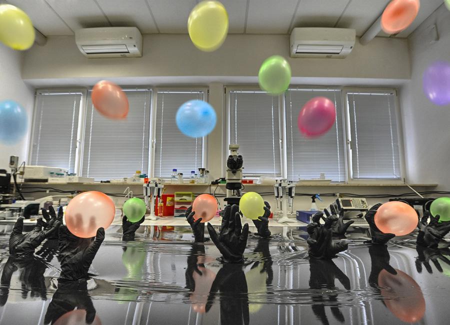 """A pictorial representation of the main idea of click chemistry used at the Institute of Physical Chemistry of the Polish Academy of Sciences, Warsaw, Poland, to bond gold nanoparticles to a carbon substrate. Nitrogen 'snap fasteners' in the carbon substrate (emerging palms) bind chemically with the carbon 'snap fasteners' on modified gold nanoparticles (here shown as a balloons). (Source: IPC PAS, Grzegorz Krzyżewski) Obrazowe przedstawienie głównej idei chemii kliknięć użytej w Instytucie Chemii Fizycznej Polskiej Akademii Nauk w Warszawie do wiązania nanocząstek złota z węglowym podłożem. Azotowe """"zatrzaski"""" w podłożu węglowym (wynurzające się dłonie) wiążą się chemicznie z węglowymi """"zatrzaskami"""" na zmodyfikowanych nanocząstkach złota (tu przedstawionych jako balony). (Źródło: IChF PAN, Grzegorz Krzyżewski)"""